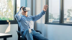 young man with virtual reality glasses to watch movies alone on headset white background