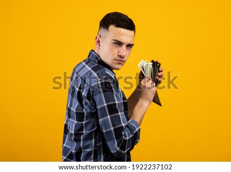 Young man with wallet full of money being greedy over his wealth on orange studio background. Millennial guy with dollars acting mean and stingy, not willing to pay taxes or share his income Foto stock ©