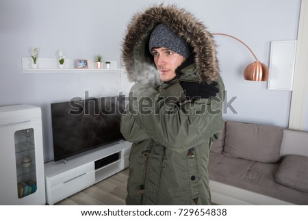 Young Man With Warm Clothing Feeling The Cold Inside House #729654838