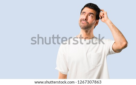 Young man with white shirt having doubts and with confuse face expression while scratching head on isolated blue background