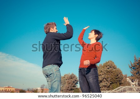 Young Man with Woman Jumping and Giving High Five