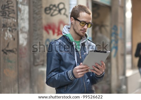 Young man with yellow glasses use tablet computer on street, public space. Blurred background