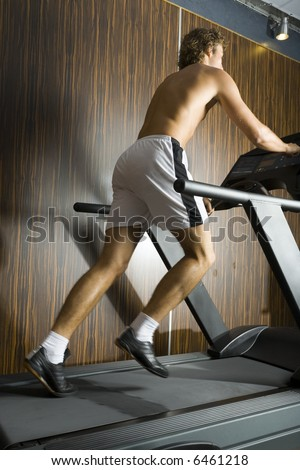 Young man without shirt running on track in gym. Whole body, rear view