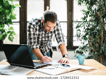 Young man work remote in cool home office. Modern workspace studio for online business and freelance creative digital project. Internet profession, shopping online, education and e learning concept.