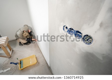 Young man, worker glueing wallpapers on concrete wall. Repair the apartment. Home renovation concept. White Wallpaper for paint #1360714925