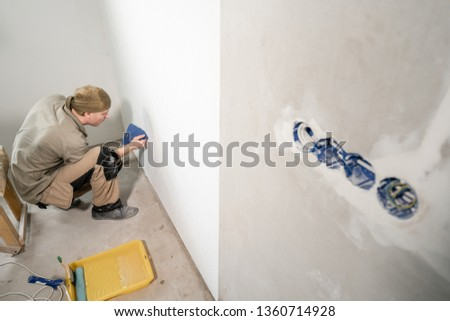 Young man, worker glueing wallpapers on concrete wall. Repair the apartment. Home renovation concept. White Wallpaper for paint #1360714928