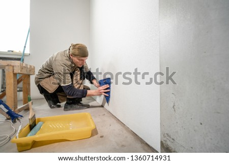 Young man, worker glueing wallpapers on concrete wall. Repair the apartment. Home renovation concept. White Wallpaper for paint #1360714931