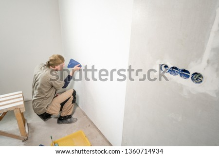 Young man, worker glueing wallpapers on concrete wall. Repair the apartment. Home renovation concept. White Wallpaper for paint #1360714934