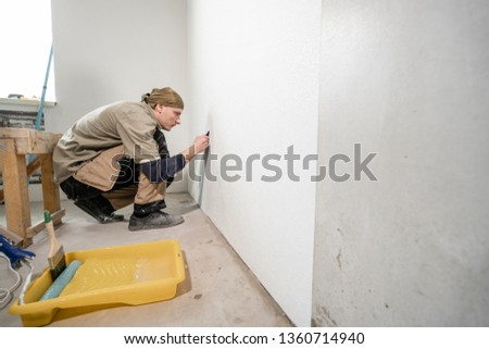 Young man, worker glueing wallpapers on concrete wall. Repair the apartment. Home renovation concept. White Wallpaper for paint #1360714940