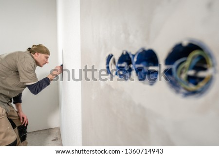 Young man, worker glueing wallpapers on concrete wall. Repair the apartment. Home renovation concept. White Wallpaper for paint #1360714943