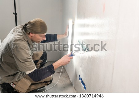 Young man, worker glueing wallpapers on concrete wall. Repair the apartment. Home renovation concept. White Wallpaper for paint