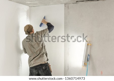 Young man, worker glueing wallpapers on concrete wall. Repair the apartment. Home renovation concept. White Wallpaper for paint #1360714973
