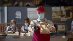 Young man worker wearing face mask and gloves giving take away meal to customer. Restaurant staff working only with take away orders during corona virus outbreak. Small business during pandemic