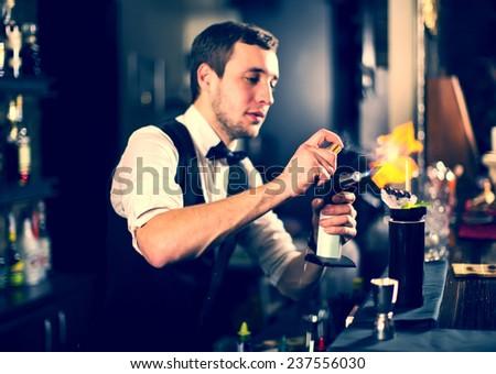 young man working as a bartender in a nightclub bar #237556030