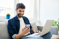 Young man working at home using laptop and smartphone
