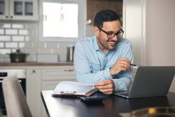 Young man working from home doing paperwork while using laptop and holding pen in his hand.