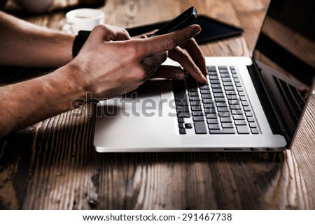 young man working from home using smart phone and notebook computer