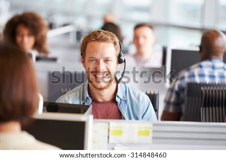 Young man working in a call centre, looking to camera