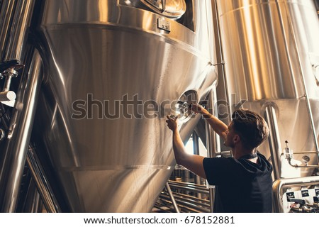 Young man working in beer manufacturing factory. Brewer working with industrial equipment at the brewery. Сток-фото ©