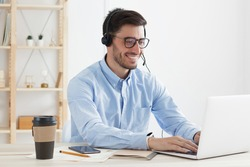 Young man working in hotline answering client inquiries and helping solve problems, feeling positive and confident, smiling happily, typing data on laptop in office