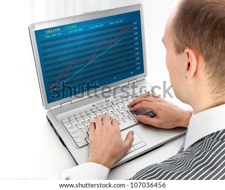 young man working of a laptop with Financial diagram