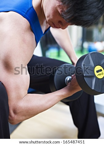 young man working on biceps with heavy dumbbell.