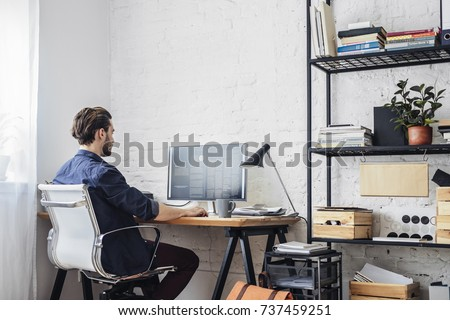 Photo of Young man working on his computer