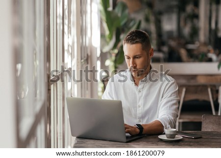 young man working on his computer at the cafe. business, freelance Stock photo ©