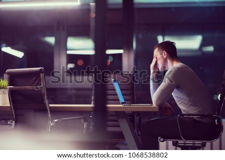 Young man working on laptop at night in dark office. The designer works in the later time. #1068538802