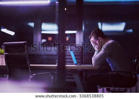Young man working on laptop at night in dark office. The designer works in the later time. #1068538805