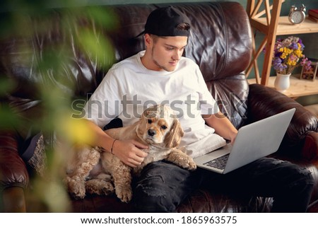 Young man working on laptop computer sitting at home with his cute dog, pet American Cocker Spaniel during coronavirus or Covid-19 quarantine. Cozy office workplace, remote work, e-learning concept.