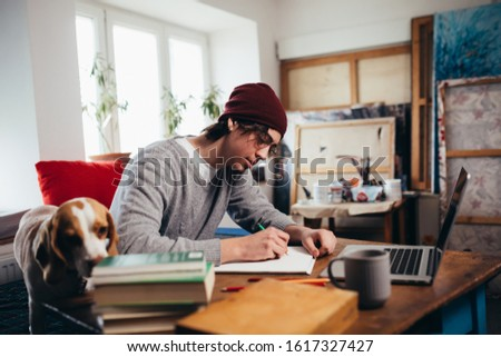 young man working on project in his room with his dog Сток-фото ©