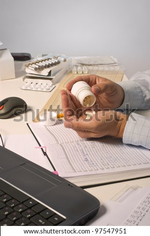 Young man working on table with computer, documents, prescriptions, counting pills. Professional clinical research monitor at working place.