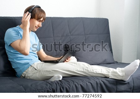 Young man working with a laptop and listening music on headphone