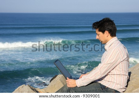 Young man working with a laptop enjoying a beautiful seascape