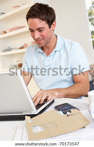 Young man working with laptop computer - stock photo