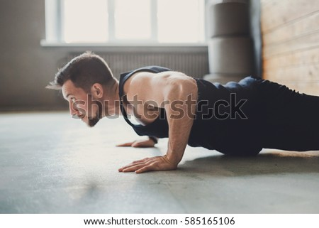 Young man workout in fitness club. Profile portrait of caucasian guy making plank or push ups exercise, training indoors