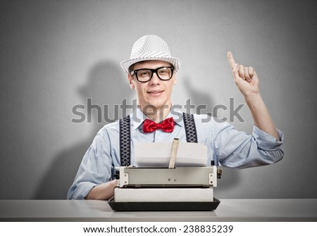 Young man writer with typing machine waiting for inspiration