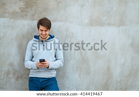 Young man writing sms standing by concrete wall. copy space stock photo