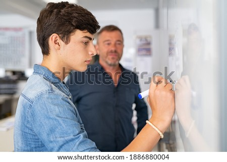 Young man writing solution of equation on whiteboard at school during math lesson with professor. College student writing on white board under the supervision of the teacher. Close up of smart guy sol Photo stock ©