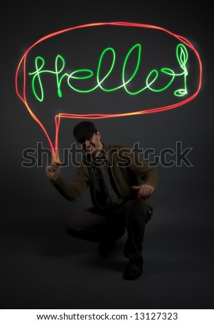"Young man writing the word ""Hello"" with light in the air, model is underexposed/ low-key to allow for the letters to stand out"