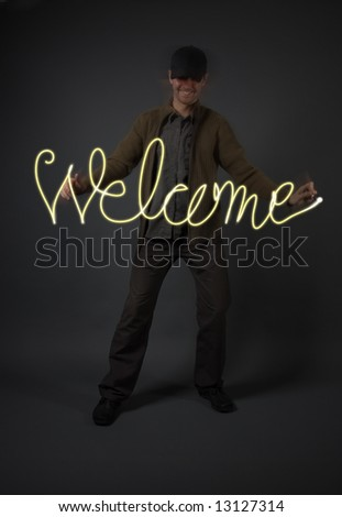 "Young man writing the word ""Welcome"" with light in the air, model is underexposed/ low-key to allow for the letters to stand out"