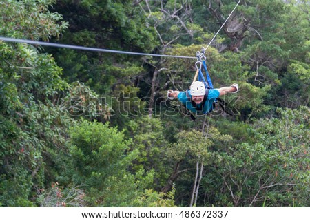 young man zooming thru a cloud forest on a zip line adventure in Monteverde Costa Rica #486372337
