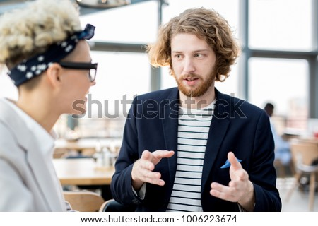 Young manager explaining his viewpoint to colleague during start-up meeting Stock foto ©