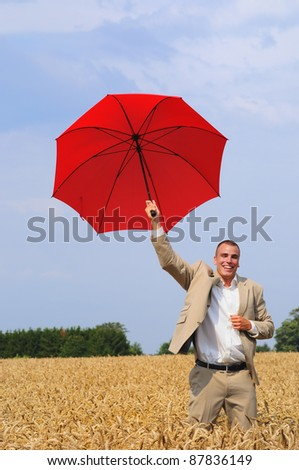 Young manager with red sun umbrella running in the wheat field happy with results of his business