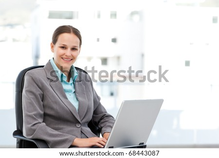 Young manager working on the laptop sitting at her desk in the office