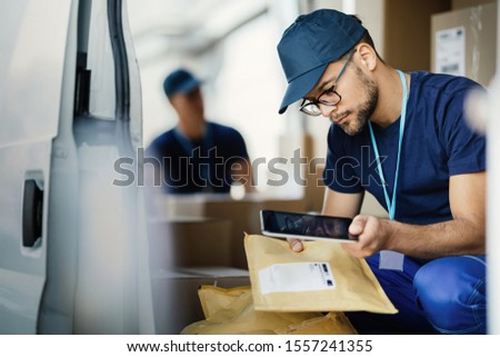 Young manual worker using digital tablet and scanning bar code on label of package in delivery van.