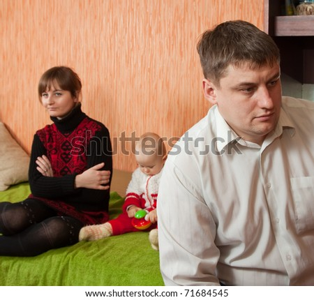 young marriage quarreling at home. Their daughter sitting between them