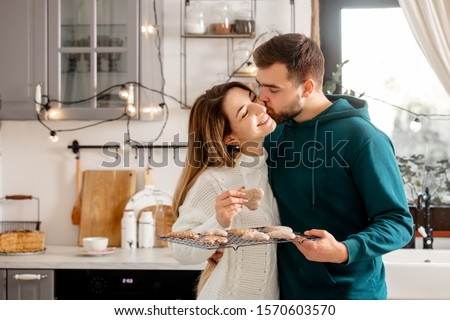 young married couple baking cookies in the kitchen