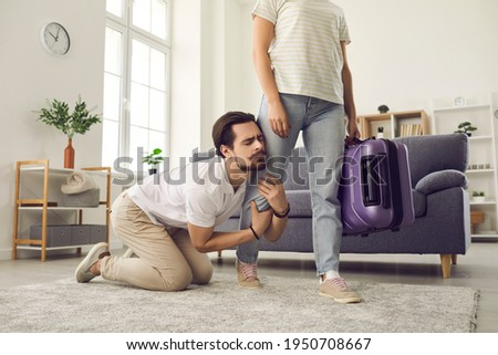 Young married couple breaking up. Angry woman leaving home with packed suitcase. Clingy desperate husband on floor holding wife's leg begging his love to stay. Relationship breakup and divorce concept Foto d'archivio ©